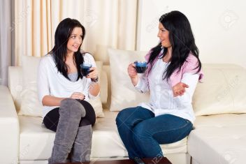 8902765-Two-beautiful-women-having-conversation-drinking-coffee-and-sitting-on-couch-home-Stock-Photo
