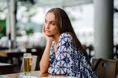 woman in white and blue top sitting in front table
