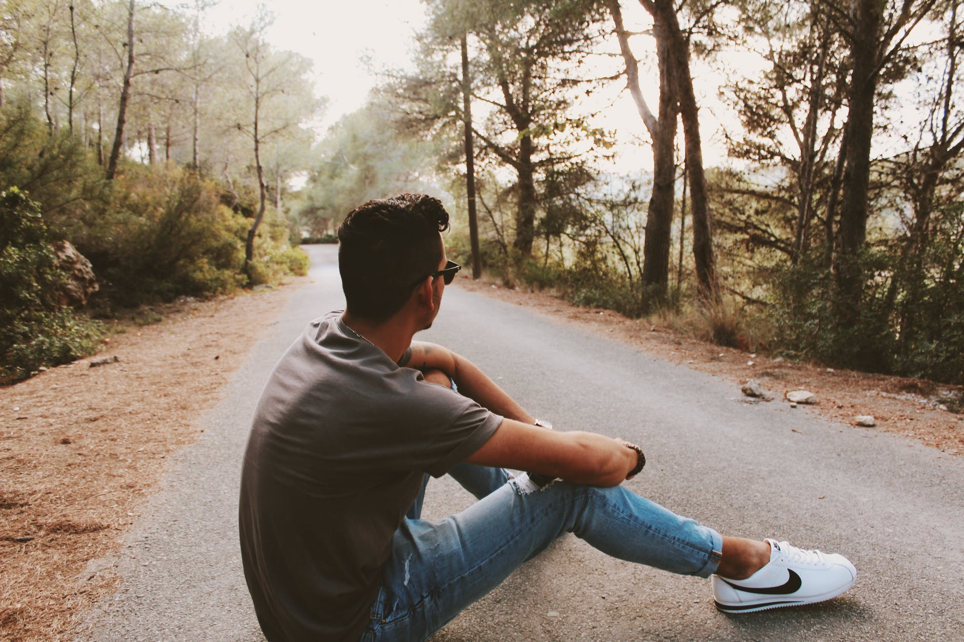 back view photo of man sitting on gray concrete road