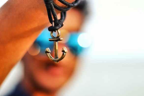 selective focus photography of anchor pendant
