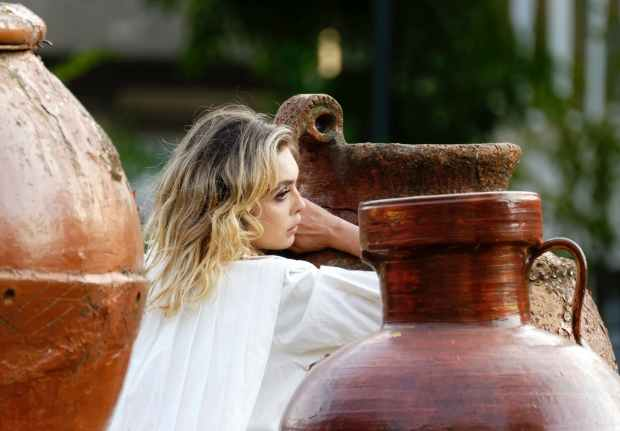 selective focus photo of woman leaning on huge jar