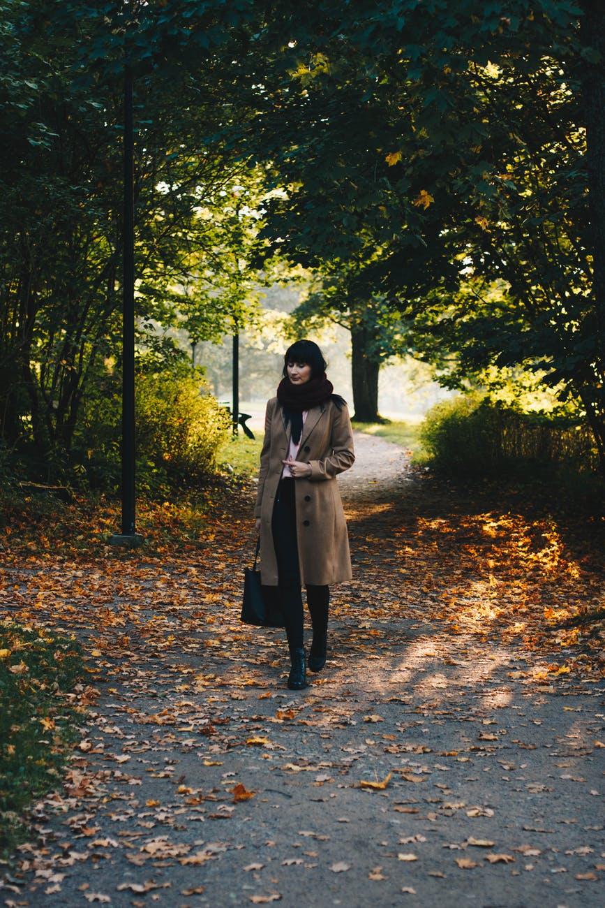 woman in coat walking in park in autumn